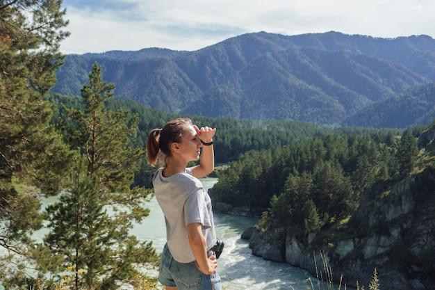 Eine junge aukasierin schaut vor dem hintergrund einer wunderschönen landschaft in die ferne
