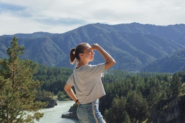 Eine junge aukasische schlanke frau schaut vor dem hintergrund einer wunderschönen landschaft in die ferne