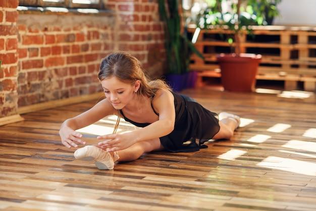 Eine junge ballerina, die im tanzsaal schnur macht.
