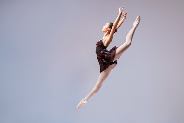 Eine junge ballerina in einem schwarzen badeanzug und spitzen sprüngen