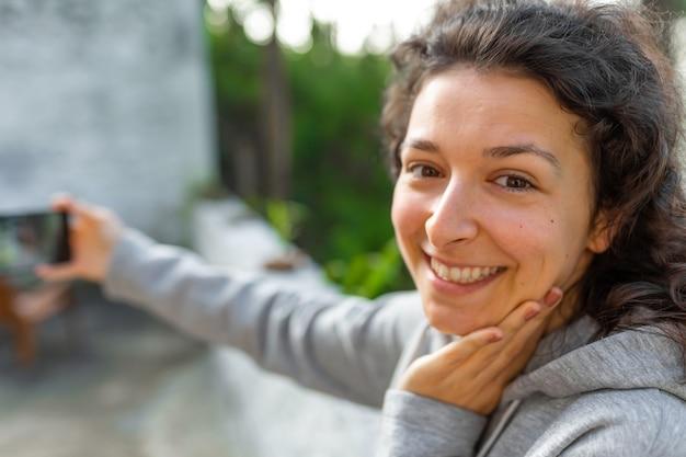 Eine junge bloggerin fotografiert sich mit einem handy. videobericht des bloggers.