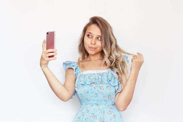 Eine junge blonde charmante frau macht ein selfie mit ihrem handy und schaut in die frontkamera