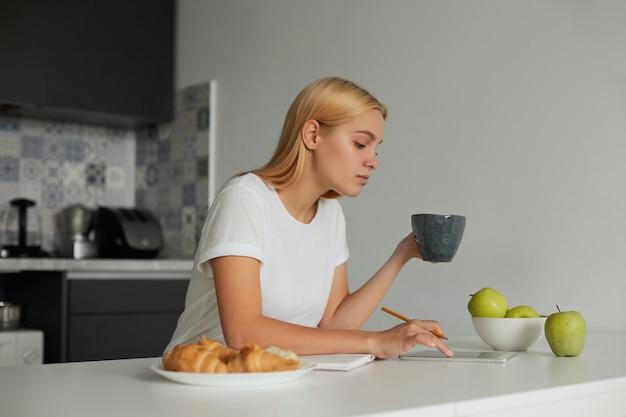 Eine junge blonde frau, die ihren tag plant, hält eine große graue tasse und führt seinen finger über den telefonbildschirm