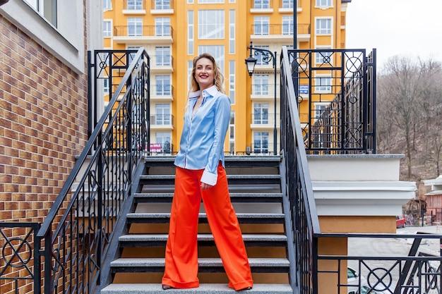 Eine junge blonde frau in bunten kleidern hält ihre hände in den taschen. das modell steht auf den stufen vor einem gelben gebäude.