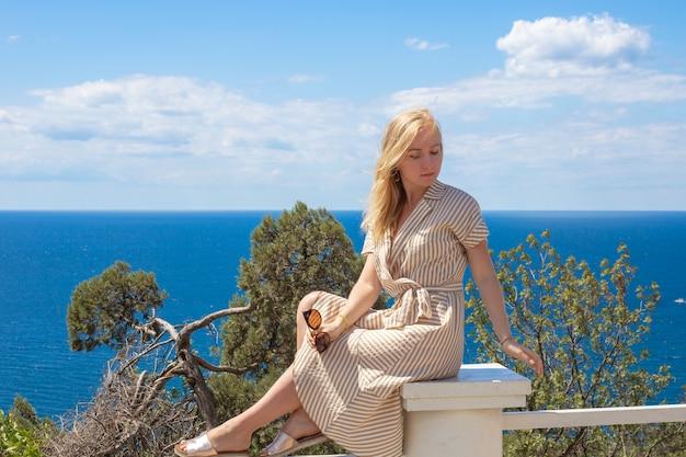 Eine junge blonde frau in einem kleid sitzt an einem sonnigen sommertag auf einem zaun auf einem hügel mit blick auf das meer und die bäume. ruhe und erholung in der natur.