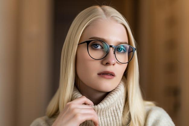Eine junge blonde frau in einem strickpullover sitzt in einem gemütlichen café