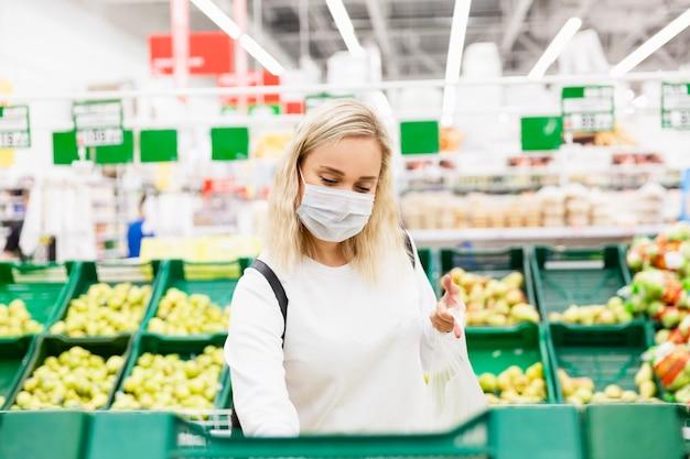 Eine junge blonde frau in einer medizinischen maske kauft früchte in einem supermarkt