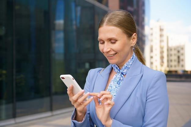 Eine junge blonde frau in einer strengen jacke entscheidet ihre angelegenheiten am telefon vor dem hintergrund eines geschäftsgebäudes. arbeitskonzept.