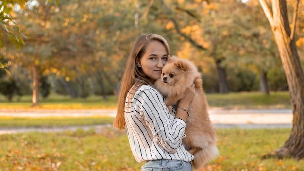 Eine junge blondine lächelt und hält einen hund in den armen.