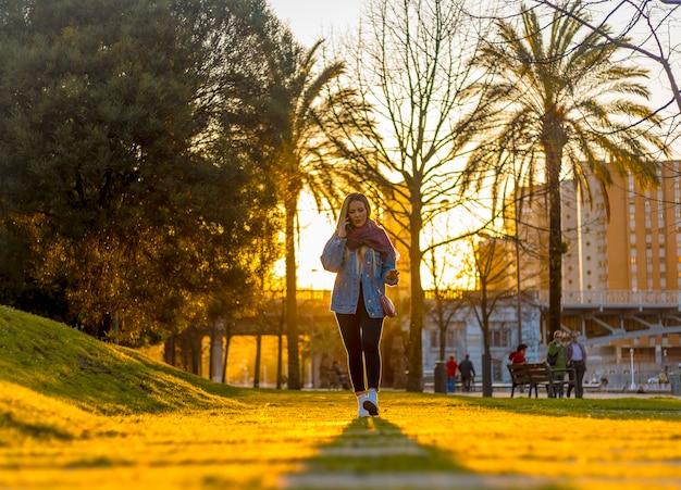 Eine junge blondine mit jeansjacke geht durch die straßen von bilbao