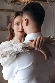 Eine junge braut in einem spitzenkleid umarmt den bräutigam.
