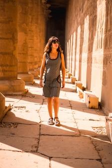 Eine junge brünette, die auf den säulen des edfu-tempels nahe der stadt assuan geht. ägypten