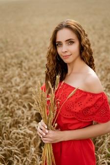 Eine junge brünette frau in einem roten sommerkleid hält ährchen auf einem weizenfeld. freiheit.