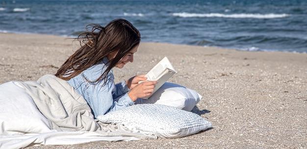 Eine junge brünette frau liegt am meer am strand, bedeckt mit einer decke, und liest ein buch. die gemütliche atmosphäre am strand, sommer