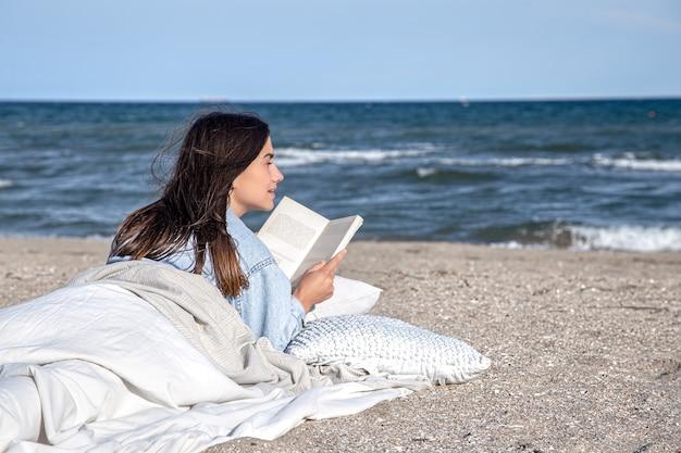 Eine junge brünette frau liegt am meer am strand, bedeckt mit einer decke, und liest ein buch. die gemütliche atmosphäre am strand, sommerkonzept.