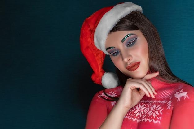 Eine junge brünette frau mit idealem kunst-make-up und einer weihnachtsmannmütze denkt nach