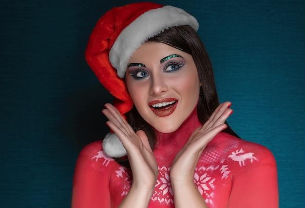 Eine junge brünette frau mit idealem kunst-make-up und einer weihnachtsmannmütze ist überrascht, bewundert