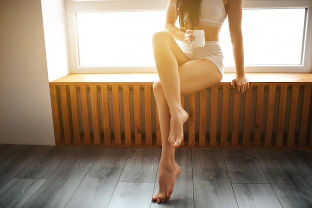 Eine junge brünette frau sitzt auf einer fensterbank und hält eine tasse tee oder kaffee in den händen. weibliches modell in weißer unterwäsche
