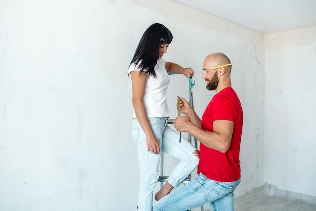Eine junge brünette frau sitzt auf einer trittleiter, und ein bärtiger mann zeigt ihre maße auf einem maßband