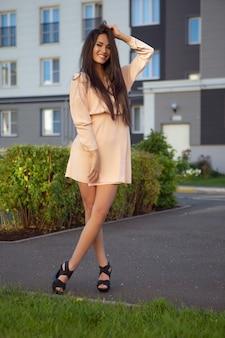 Eine junge brünette in einem leichten sommerkleid posiert draußen an einem warmen tag