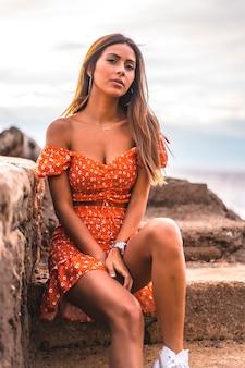 Eine junge brünette kaukasische frau in einem roten kleid am strand von itzurrun in der stadt zumaia, gipuzkoa. baskenland. lifestyle-sitzung, auf der seetreppe sitzen