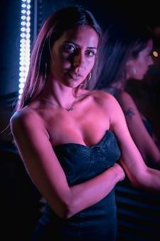 Eine junge brünette kaukasische frau in einem schwarzen kleid beleuchtet durch lila led-licht, das in schwarzen kristallen reflektiert wird und die kamera betrachtet. nachtstadtfotografie