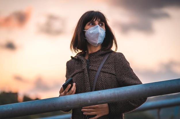 Eine junge brünette mit einer maske auf einem sonnenuntergang auf einer brücke. erste spaziergänge der unkontrollierten covid-19-pandemie