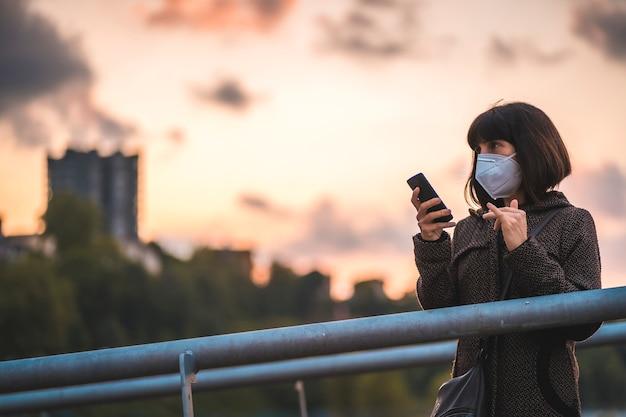 Eine junge brünette mit einer maske auf einem sonnenuntergang, der eine audio-nachricht sendet. erste spaziergänge der unkontrollierten covid-19-pandemie