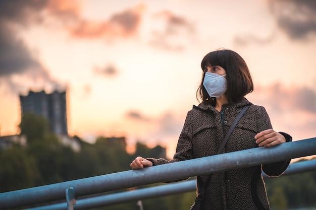 Eine junge brünette mit einer maske auf einem sonnenuntergang genießt die ersten spaziergänge. erste spaziergänge der unkontrollierten covid-19-pandemie