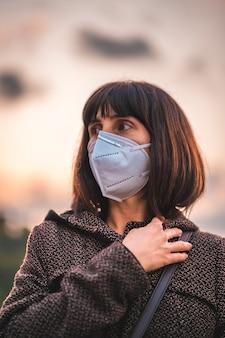 Eine junge brünette mit maske. erste spaziergänge der unkontrollierten covid-19-pandemie