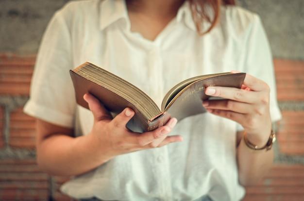 Eine junge christin schließt am sonntag in ihrem zimmer ihre heiligen schriften, liest und studiert.
