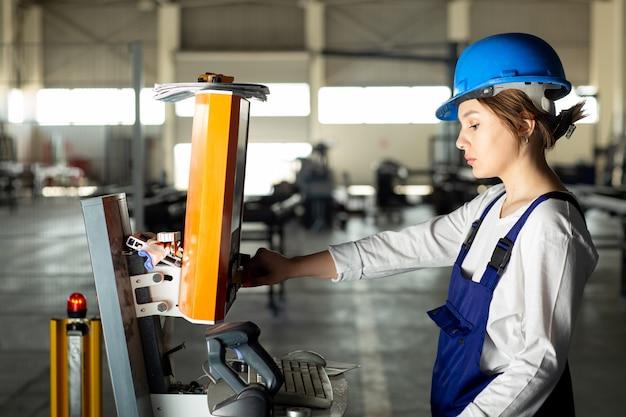 Eine junge dame der vorderansicht im blauen bauanzug und im helm, die maschinen im hangar während des architekturbaus der tagesgebäude steuern
