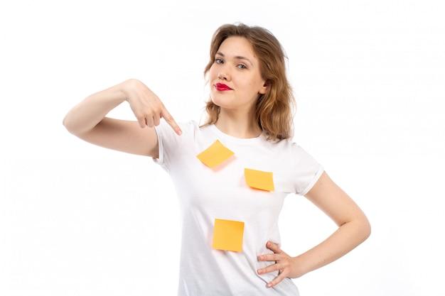 Eine junge dame der vorderansicht im weißen hemd mit orangefarbenen noten und schwarzen modernen jeans, die lächelnd auf dem weiß aufwerfen