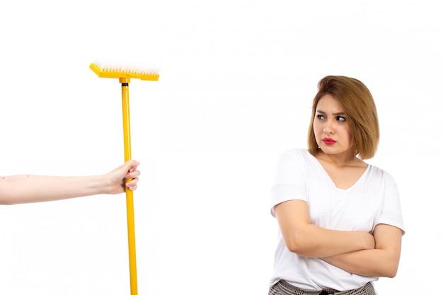 Eine junge dame der vorderansicht im weißen hemd und in der hellen modernen hose, die gelben mopp erhalten, missfiel auf dem weiß