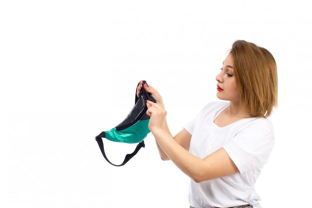 Eine junge dame der vorderansicht im weißen hemd und in der hellen modernen hose, die kleine tasche auf dem weiß fixiert
