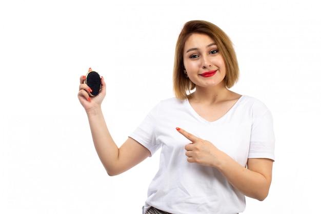 Eine junge dame der vorderansicht im weißen hemd und in der hellen modernen hose, die schwarze kleine haarbürste auf dem weiß hält