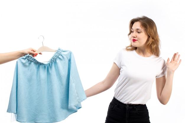 Eine junge dame der vorderansicht im weißen hemd und in der schwarzen hose, die blauen rock auf dem weiß erhalten