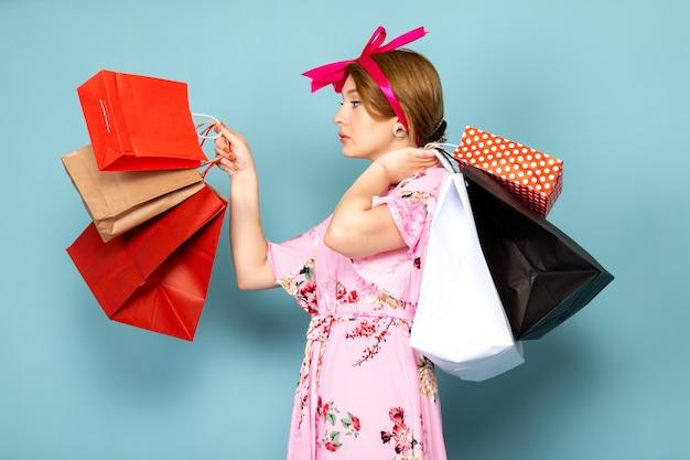 Eine junge dame der vorderansicht in der blume entwarf rosa kleid, das einkaufspakete auf blau hält