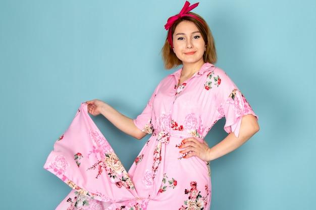Eine junge dame der vorderansicht in der blume entwarf rosa kleid, das mit lächeln auf ihrem gesicht auf blau aufwirft