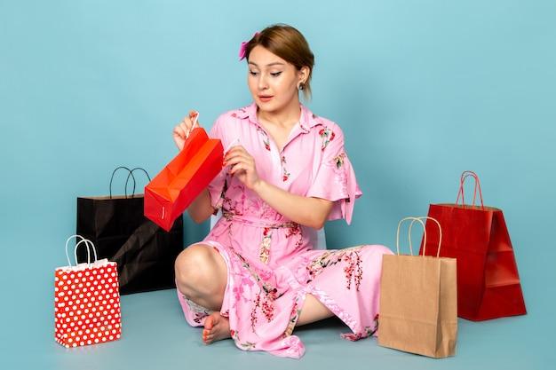 Eine junge dame der vorderansicht in der blume entwarf rosa kleid sitzend und posierend mit einkaufspaketen auf blau