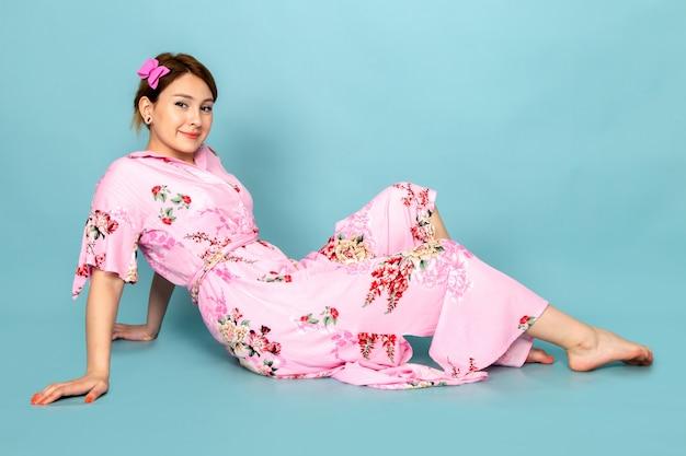 Eine junge dame der vorderansicht in der blume entwarf rosa kleid sitzend und posierend mit lächeln auf blau