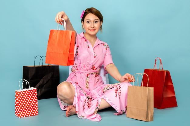 Eine junge dame der vorderansicht in der blume entwarf rosa kleid sitzend und posierend mit lächeln und einkaufspaketen auf blau