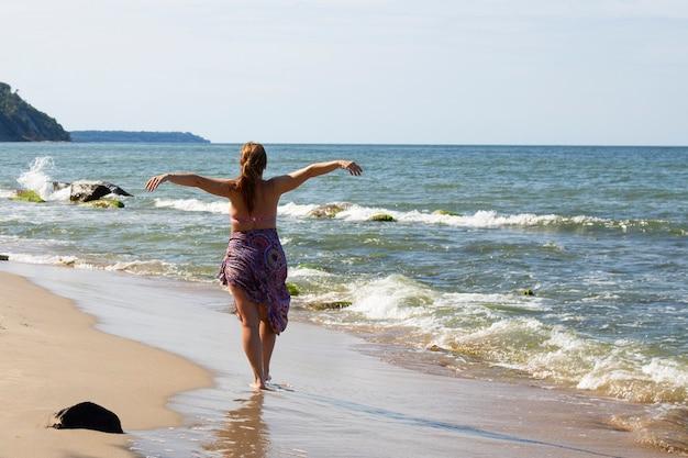 Eine junge dame, die mit dem rücken zur kamera in einem pareo am meer steht, sonnt sich. ostsee