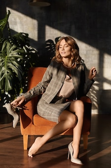 Eine junge dame in elegantem blazer und rock sitzt auf einem stuhl, zieht ihre schuhe aus und genießt das gefühl der entspannung im büroraum.