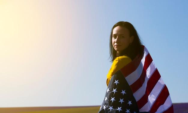 Eine junge, dunkelhaarige frau, die die flagge der vereinigten staaten von amerika gegen den sonnigen himmel hält. memorial day und usa independence day konzept.