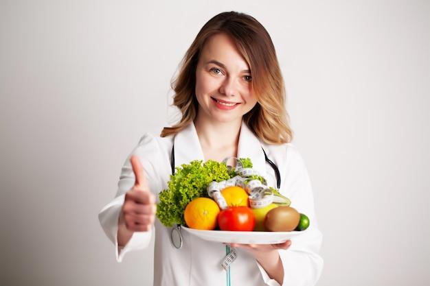 Eine junge ernährungsberaterin hält in ihren händen frisches gemüse und obst auf dem teller im sprechzimmer