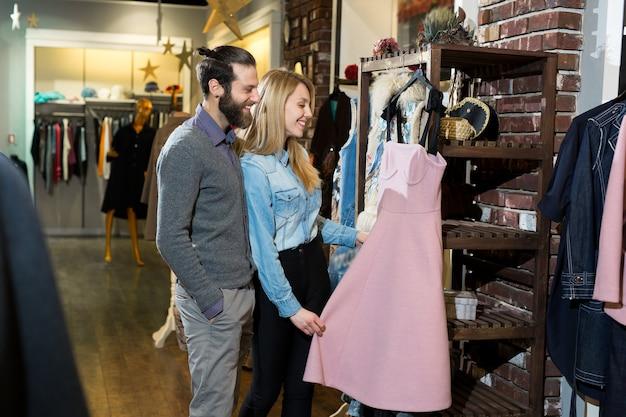 Eine junge familie, ein mann und eine frau, die ein rosa kleid in einem bekleidungsgeschäft umarmen und wählen.