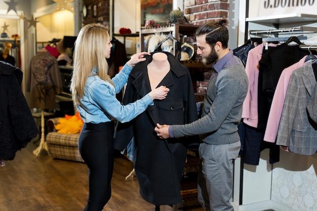 Eine junge familie, ein mann und eine frau umarmen sich und wählen einen schwarzen mantel in einem bekleidungsgeschäft.