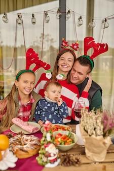 Eine junge familie feiert weihnachten im landhaus
