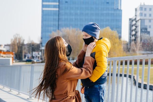 Eine junge familie geht an einem sonnigen tag während einer quarantäne und pandemie spazieren und atmet frische luft. masken auf den gesichtern der menschen.